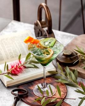 Vista superior do copo de cocktail verde com casca de banana de raspas de laranja e fatia de kiwis