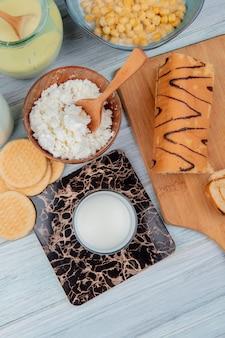 Vista superior do copo de leite com biscoitos, leite condensado, queijo cottage, rolo de cereais na mesa de madeira