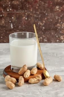 Vista superior do copo de vidro com leite na bandeja de madeira e colher de frutas secas na mesa branca na parede marrom