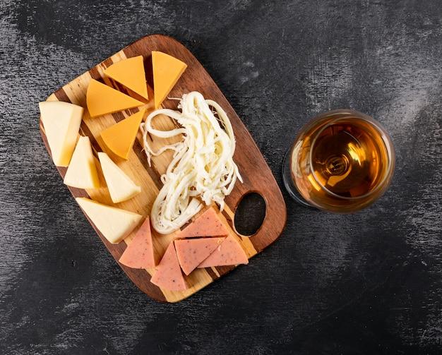 Vista superior do copo de vinho e queijo na tábua de madeira no escuro horizontal