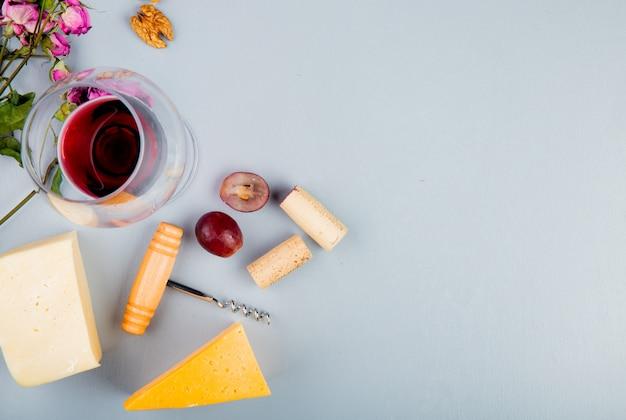Vista superior do copo de vinho tinto com rolhas de uva de queijo saca-rolhas de nozes e flores em branco com espaço de cópia