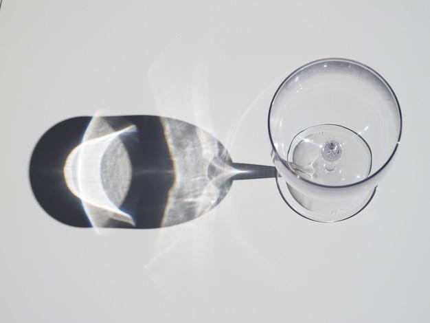 Vista superior do copo de vinho vazio com sombra na mesa branca durante o dia ensolarado.