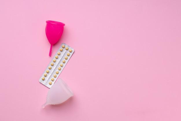 Vista superior do copo menstrual e pílulas anticoncepcionais orais