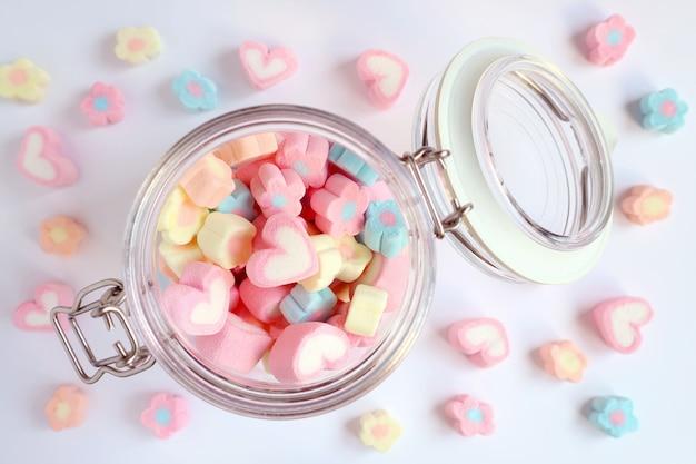 Vista superior do coração de cor pastel e doces de marshmallow em forma de flor em um frasco de vidro