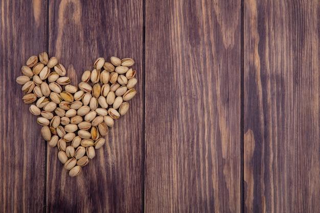 Vista superior do coração de pistache em forma de superfície de madeira