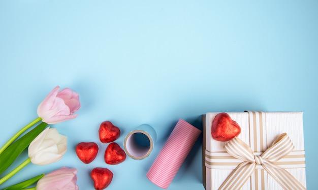 Vista superior do coração de tulipas cor de rosa em forma de bombons de chocolate embrulhados em papel vermelho, caixa de presente e rolo de papel colorido na mesa azul com espaço de cópia