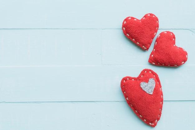 Vista superior do coração rosa e vermelho artesanal sobre fundo azul de madeira