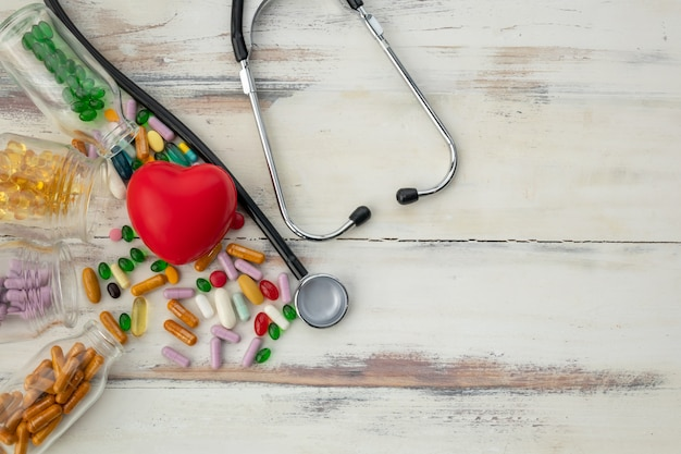Vista superior do coração vermelho e medicamento no piso de madeira
