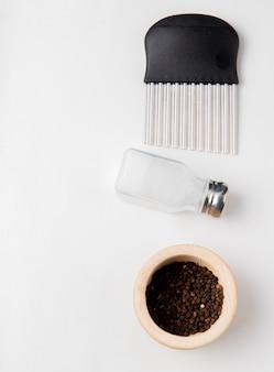 Vista superior do cortador de batatas fritas com sementes de sal e pimenta preta na superfície branca com espaço de cópia
