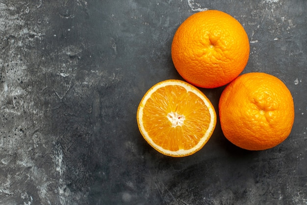 Vista superior do corte da fonte de vitamina e laranjas frescas inteiras em fundo cinza