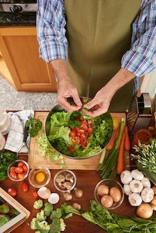 Vista superior do cozinheiro irreconhecível, adicionando salsa à saladeira