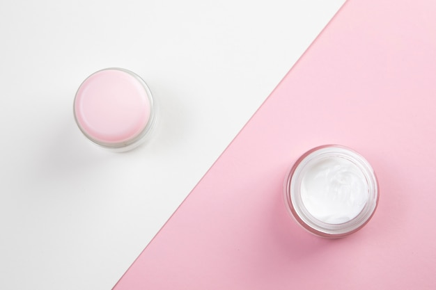 Vista superior do creme corporal em fundo rosa e branco