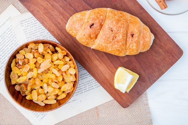 Vista superior do croissant com um pedaço de limão em uma tábua de madeira e passas secas em uma tigela de madeira em branco