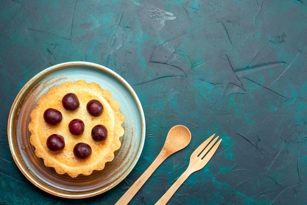 Vista superior do cupcake com deliciosas cerejas ao lado da colher e do garfo
