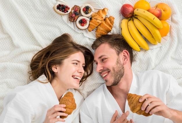 Vista superior do cupê na cama com frutas e croissants