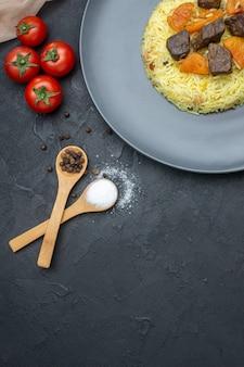 Vista superior do delicioso arroz pilaf cozido com fatias de carne e tomate na superfície escura