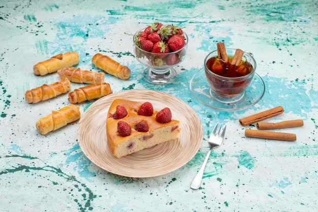 Vista superior do delicioso bolo de morango fatiado em fatias de bolo com chá de canela e pulseiras em uma mesa azul brilhante, bolo de frutas vermelhas