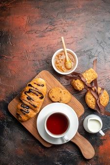 Vista superior do delicioso croisasant, uma xícara de chá preto em uma tábua de madeira, biscoitos de mel empilhados com leite em uma superfície escura