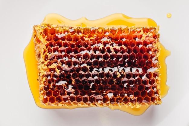 Vista superior do delicioso favo de mel na placa brilhante sobre madeira clara