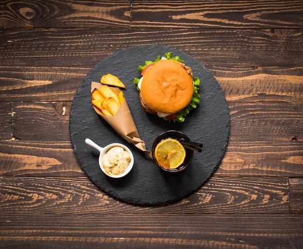 Vista superior do delicioso hambúrguer com legumes em um fundo de madeira.