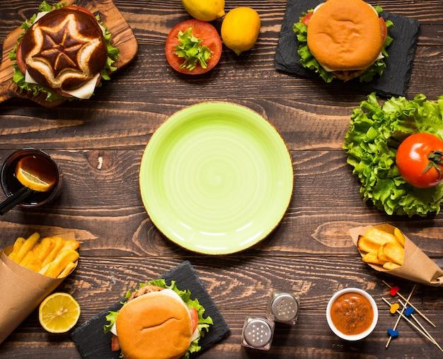 Vista superior do delicioso hambúrguer, com legumes, em uma mesa de madeira