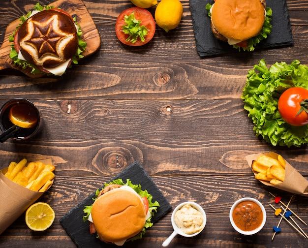 Vista superior do delicioso hambúrguer, com legumes, sobre um fundo de madeira.
