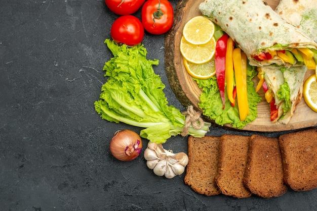 Vista superior do delicioso sanduíche de carne shaurma fatiado com pão e vegetais em cinza preto
