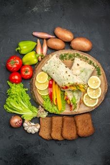 Vista superior do delicioso sanduíche de carne shaurma fatiado com pão e vegetais na mesa preta