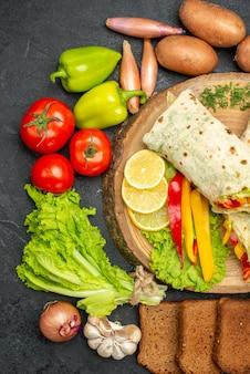 Vista superior do delicioso sanduíche de carne shaurma fatiado com pão e vegetais no preto
