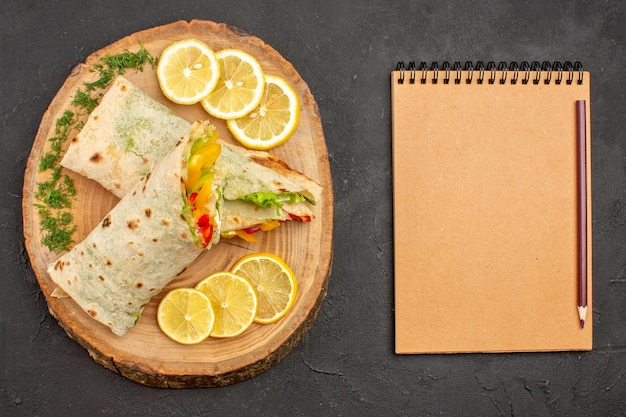 Vista superior do delicioso sanduíche de carne shaurma fatiado com rodelas de limão na mesa preta