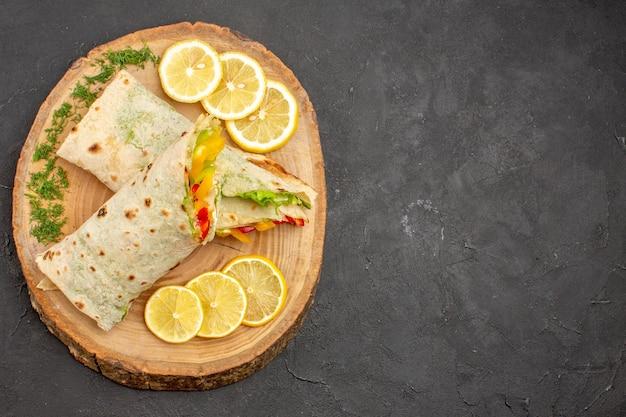 Vista superior do delicioso sanduíche de carne shaurma fatiado com rodelas de limão no preto