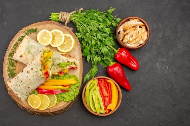 Vista superior do delicioso sanduíche de frango fatiado shaurma com limão e verduras no escuro
