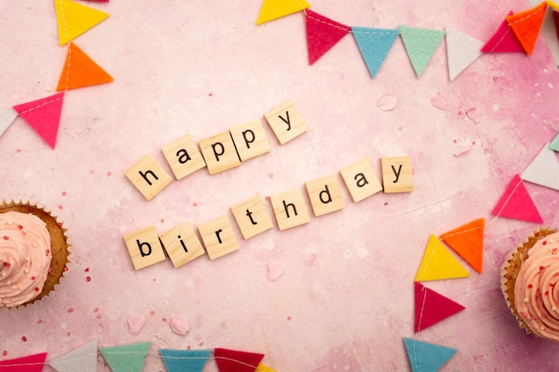Vista superior do desejo de feliz aniversário em letras de madeira com guirlandas e cupcakes