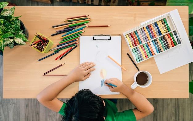 Vista superior do desenho da criança com lápis de cor em papel branco sobre uma mesa de madeira.