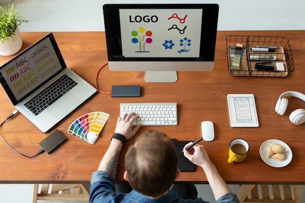 Vista superior do designer de logotipo sentado na mesa e editando o design do ícone usando o bloco de desenho