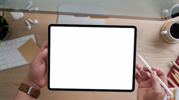Vista superior do designer usando tablet enquanto trabalhava na sala de escritório rústico moderno com computador e material de escritório