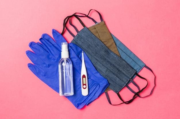 Vista superior do desinfetante para as mãos com álcool, luvas de látex, termômetro digital e máscaras reutilizáveis feitas à mão na superfície rosa