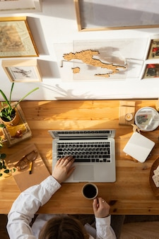 Vista superior do desktop de madeira, mãos de designer de mulher usando laptop e segurando uma xícara de café. local de trabalho do freelancer.