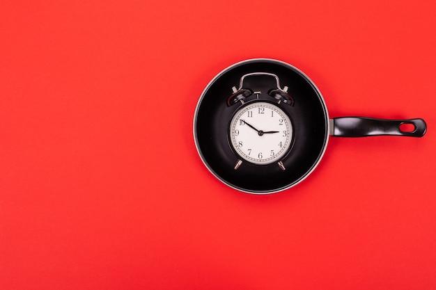 Vista superior do despertador na panela isolada em vermelho