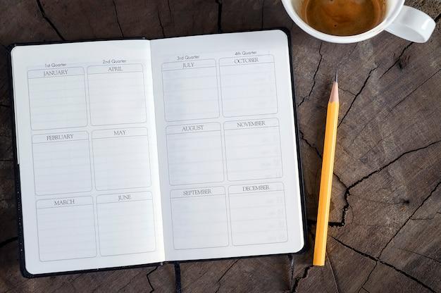 Vista superior do diário aberto da página com lápis e a xícara de café amarelos no fundo de madeira.
