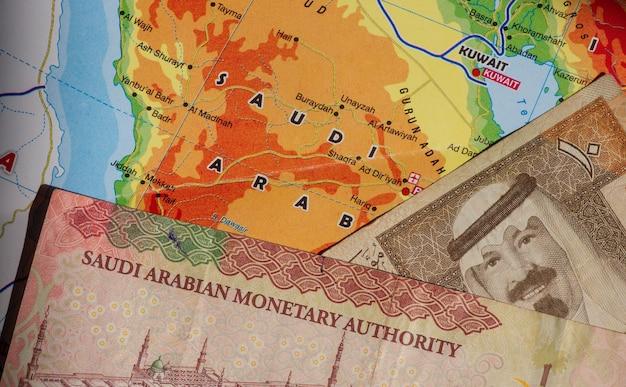 Vista superior do dinheiro, da nota de riyal da arábia saudita e do mapa da arábia saudita para segundo plano. conceito de negócios, finanças, economia e investimento