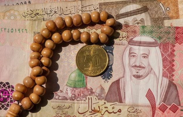 Vista superior do dinheiro, da nota e da moeda dos riais da arábia saudita e contas de oração, em foco superficial
