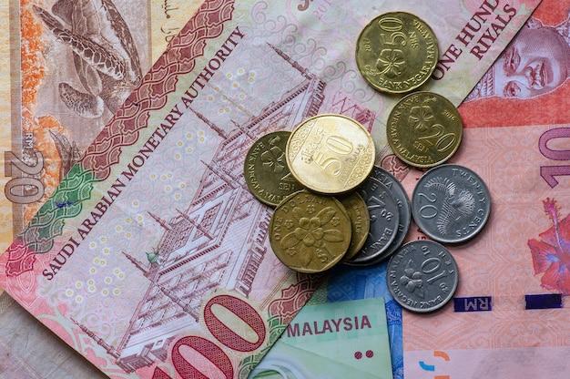 Vista superior do dinheiro, notas de ringgit da malásia, dólar de cingapura e riais da arábia saudita para segundo plano. conceito de negócios, finanças, economia e investimento