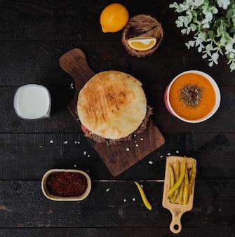 Vista superior do doner kebab no pão pita em uma placa de madeira, servido com sopa de lintel ayran bebida e em conserva pimentas verdes quentes na parede de madeira