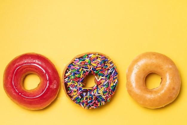 Vista superior do donut com cobertura de chocolate com granulado, donut com cobertura de açúcar e morango com cobertura em fundo amarelo.
