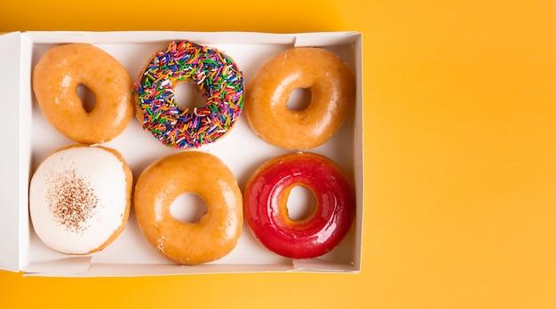 Vista superior do donut com cobertura de chocolate com granulado, donut com cobertura de açúcar e morango