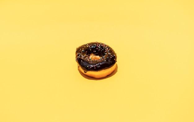 Vista superior do donut com coberturas coloridas sobre fundo de cor pastel.
