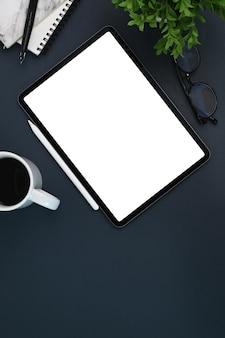 Vista superior do elegante espaço de trabalho com mesa digital, xícara de café, planta de casa e caderno em couro preto.