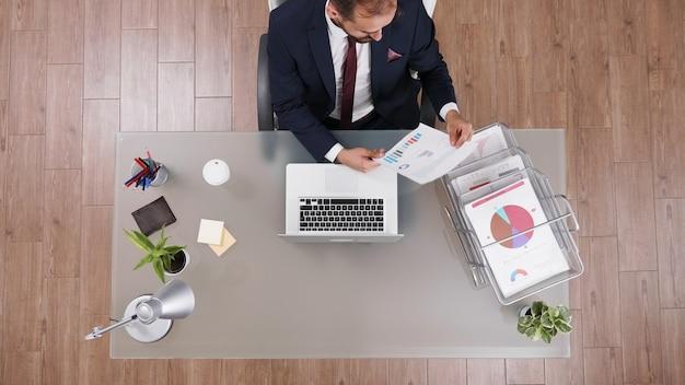 Vista superior do empresário analisando documentos de estatísticas da empresa, trabalhando na estratégia financeira