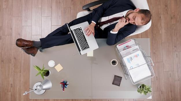 Vista superior do empresário de terno mantendo os pés na mesa enquanto digita as estatísticas da empresa